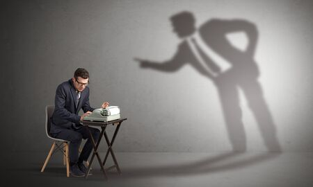 Photo pour Little man working and a big shadow arguing with him - image libre de droit