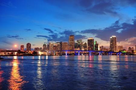 Foto de Miami city skyline panorama at dusk with urban skyscrapers and bridge over sea with reflection - Imagen libre de derechos