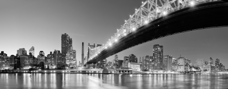 Photo pour Queensboro Bridge over New York City East River black and white at night with river reflections and midtown Manhattan skyline illuminated.  - image libre de droit