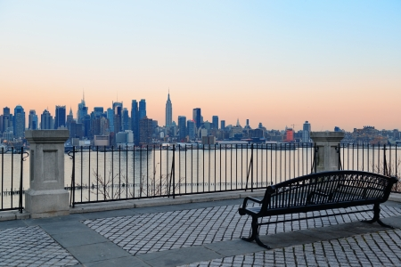 Photo pour Bench in park and New York City midtown Manhattan at sunset with skyline panorama view over Hudson River - image libre de droit