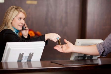 Young Receptionist giving room keys to customer at reception in hotel