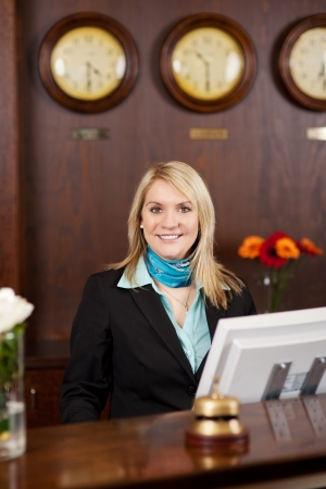 smiling blond receptionist behind the counter in hotel
