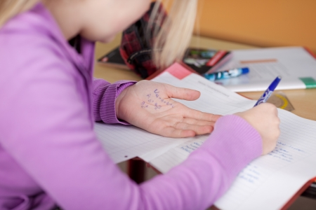 Midsection of female student copying from cheat sheet on hand at desk