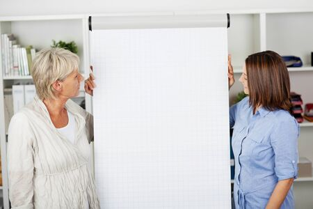 An elderly and young females looking at the flipchart in office.