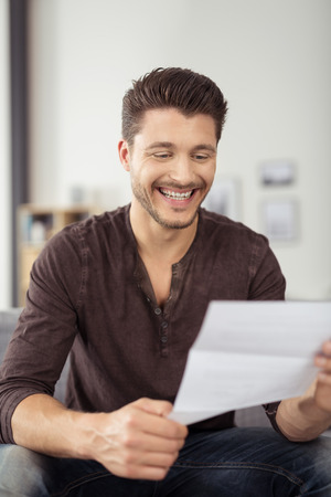 Close up Cheerful Handsome Young Guy Sitting at the Couch, Laughing While Reading a Letter from a Friend