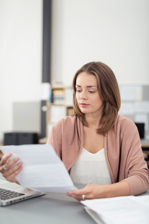 Portrait of an Attractive Young Office Woman Sitting at her Worktable Reading a Letter with Serious Facial Expression.