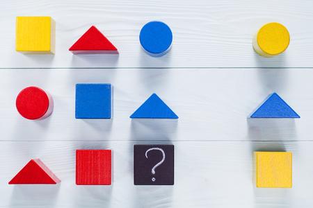 Foto de IQ test. Choose correct answer. Logical tasks composed of geometric wooden shapes.  Children's educational logical task, flat lay. - Imagen libre de derechos