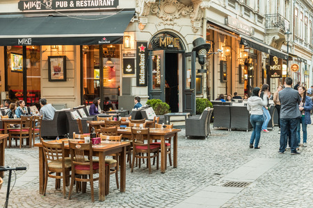 Photo for BUCHAREST ROMANIA  MAY 31 2015: Tourists Visiting And Having Lunch At Outdoor Restaurant Cafe Downtown Lipscani Street one of the most busiest streets of central Bucharest. - Royalty Free Image