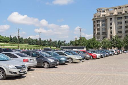 Foto de BUCHAREST, ROMANIA - JULY 26, 2015: Cars In Car Parking Lot In Front Of Parliament Palace Casa Poporului Or House Of The People In Bucharest. - Imagen libre de derechos