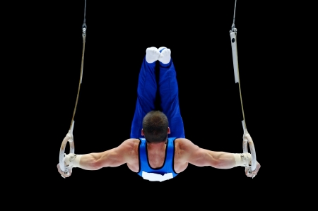 Photo pour Back view with a gymnast performing on the rings apparatus - image libre de droit