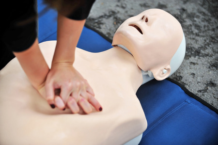 Foto de Hands of a woman are seen on a mannequin during an exercise of resuscitation - Imagen libre de derechos