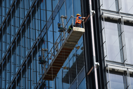 Photo pour Construction workers on a suspended platform on a skyscraper glass facade - image libre de droit