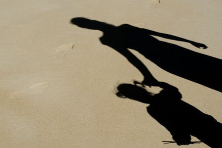 Photo pour Shadow of mother and her child over a sand on the beach during summer vaction. - image libre de droit