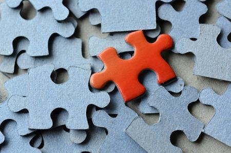 Photo pour Orange puzzle pice standing above the rest of puzzle pieces.  - image libre de droit