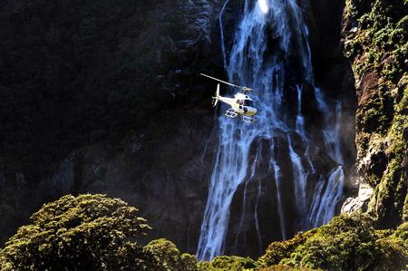 Foto de A helicopter flies over Fiordland, southern New Zealand. - Imagen libre de derechos