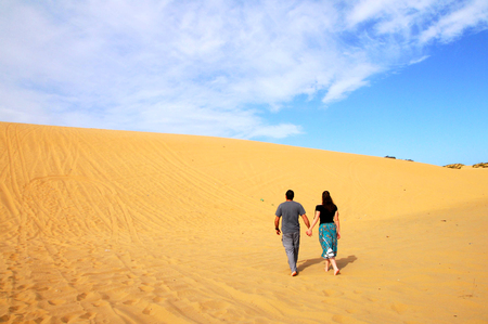 A couple climbs to the top of the Great Sand Dune near Ashdod, Israel.