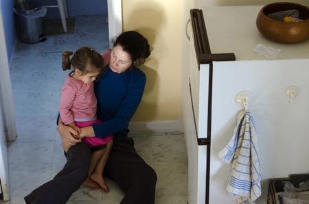Foto de Sad, hungry poor little girl and her mother site on the floor in their home kitchen. - Imagen libre de derechos
