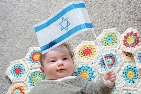 Photo for An Israeli newborn baby holding the Israeli flag. Concept photo Israel, Israeli , citizen, patriotism, family, childhood, fertility rate. - Royalty Free Image