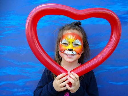 Little child (girl age 5-6)  with lion face painting  holding balloon in a shape of heart