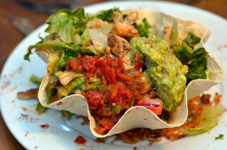 Photo for Mexican food - tostada salad. Lemon chicken guacamole,salas sauce and  rise in  tortilla. - Royalty Free Image