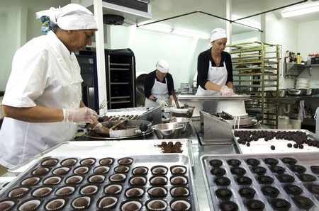 Photo pour KERIKERI, NZ - JAN 07: Chocolate factory worker prepares dipped Chocolate balls on Jan 07 2014.In 2006 more than 6.5 million tons of chocolate was traded worldwide. - image libre de droit