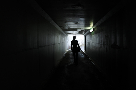Photo for Silhouette of a young woman walks alone in a dark tunnel. Violence against women concept. Real people, copy space - Royalty Free Image