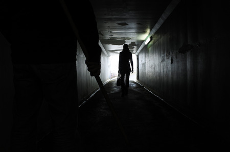 Photo for Silhouette of a man carries a wooden stick and follows a young woman in a dark tunnel. Violence against women concept. Real people, copy space - Royalty Free Image