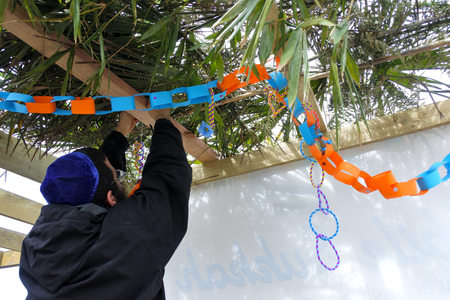 Photo pour Jewish Orthodox man decorating a Sukkah on sukkot Feast of Tabernacles, Feast of the Ingathering or Feast of booths. Copy space - image libre de droit