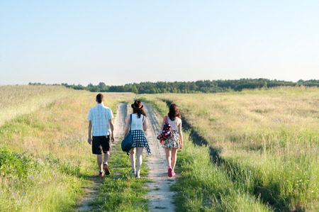 Photo for Young people walking away along country path - Royalty Free Image