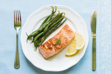 Foto per Grilled salmon fillet with green beans and lemon on white plate from above - Immagine Royalty Free