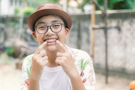 Photo pour Asia teenager with teeth brace dental smiling and happy for lifestyle or healthcare concept background in Vintage tone. - image libre de droit