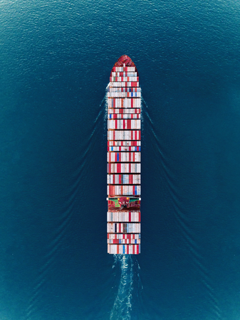 Foto de Aerial top view container ship on the sea full load container for import export, shipping or transportation. - Imagen libre de derechos