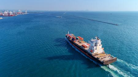 Foto de Aerial view container ship going to sea port for import export, shipping or transportation concept background. - Imagen libre de derechos