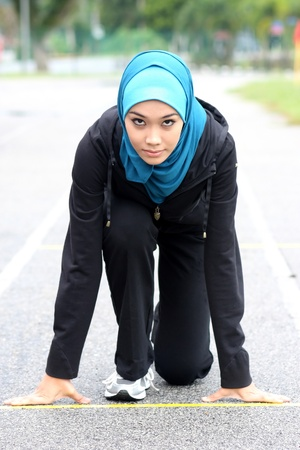 Photo for Athletic muslim woman on track starting to run  - Royalty Free Image