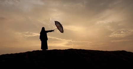 silhouettes of muslim women with umbrella during sunset