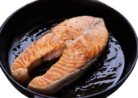 Foto de Salmon steak on black frying pan. with oil Tasty roasting fish on white background - Imagen libre de derechos