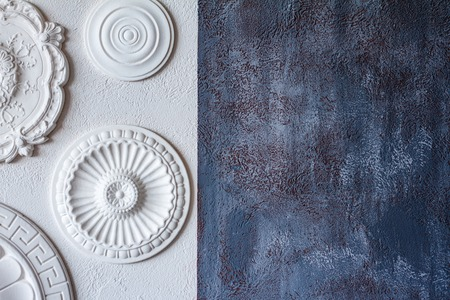 Photo for A two-color background, gray decorative plaster and a white wall with several white ceiling rosettes. - Royalty Free Image
