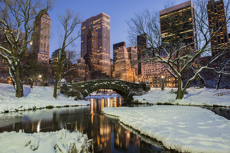 Foto de New York City Manhattan Central Park in winter with snow, Gapstow bridge; freezing lake and skyscrapers at dusk   - Imagen libre de derechos