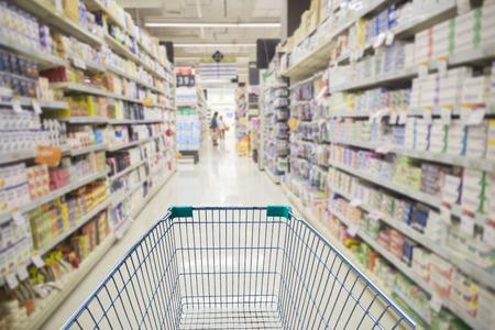 Photo pour Supermarket interior, empty green shopping cart - image libre de droit