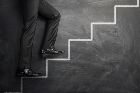 Businessman climbing at the career stairs drawn on a black chalkboard with copy space