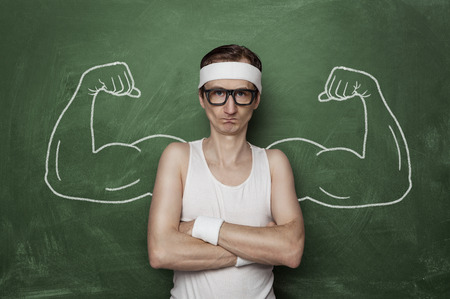 Funny sport nerd with fake muscle drawn on the chalkboard