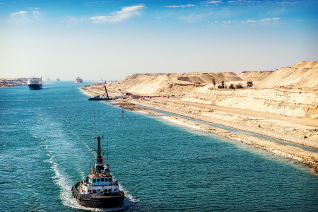 Photo pour The Suez Canal - a ship convoy passes through the new eastern extension canal, opened August 2015,  a tugboat in the foreground - image libre de droit