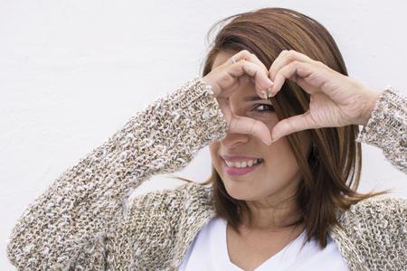 Foto de Woman laughing while showing heart with her hands. - Imagen libre de derechos