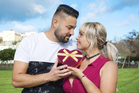 Foto de Couple in love with a gift in the form of heart. - Imagen libre de derechos
