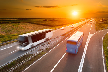 Foto de Two buses on highway in motion blur at sunset - Imagen libre de derechos