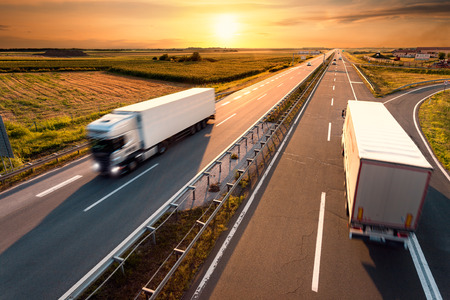 Photo pour Two trucks on highway in motion blur at sunset - image libre de droit