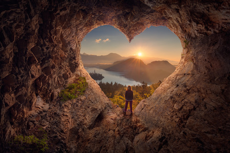 Foto de Lone woman enjoying in beautiful mountain nature, celebrating freedom and standing on edge of the cliff against the rising sun. Valentines day concept. - Imagen libre de derechos