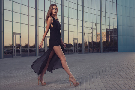 Photo for Walking woman in long black dress - Royalty Free Image