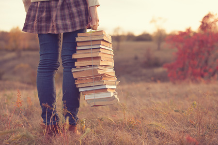 Photo pour Hipster girl holding a stack of books - image libre de droit