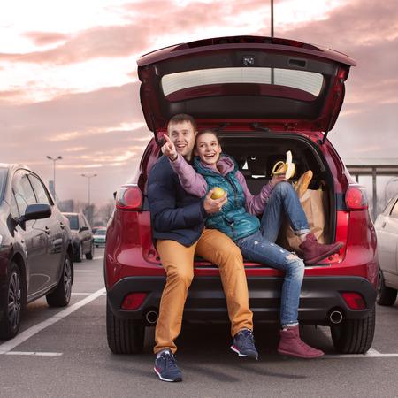 Photo pour Happy couple sitting at car trunk after shopping - image libre de droit